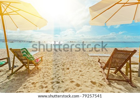 Chairs on white sand beach. - stock photo