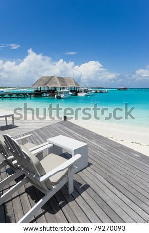 chairs on wooden deck towards the sea in maldives island resort