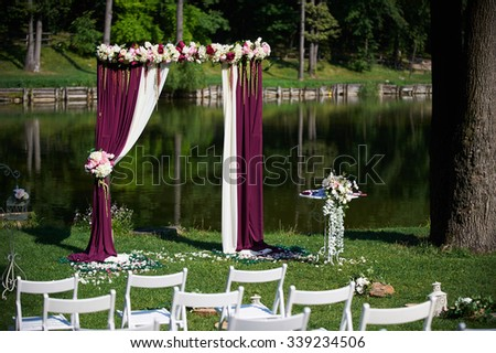 chairs set in rows for the wedding ceremony. chairs white. They are decorated for the festive event. chairs are on the green lawn outside with wedding arch in the background