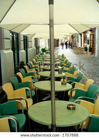 Chairs, tables and parasolars of a cafe in a row.