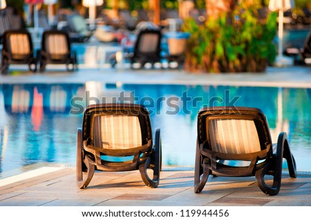 Chaise lounge by the pool to relax in the villa. - stock photo