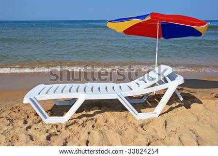 Chaise lounge with an umbrella on a beach against the sea - stock photo
