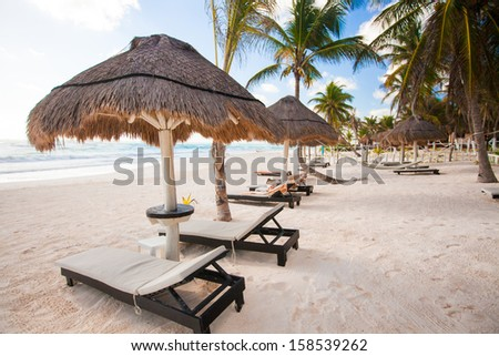 Chaise lounges under an umbrella on white sandy beach - stock photo