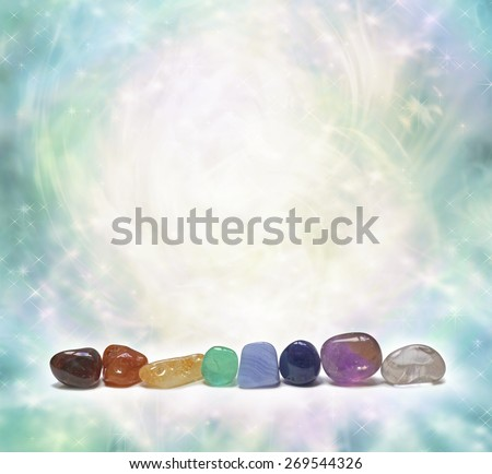 Chakra Crystals emitting beautiful energy - a row of chakra colored tumbled semi precious gemstones on a swirling sparkling ethereal pastel colored background with plenty of copy space - stock photo
