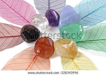 Chakra stones, close up - Chakra crystals laid on skeleton leaves forming a flower shape on white background - stock photo