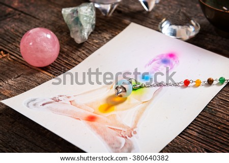 Chakras illustrated over human body with natural crystals and pendulum - stock photo