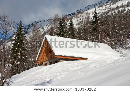 Chalet covered with snow in the French Alps - stock photo