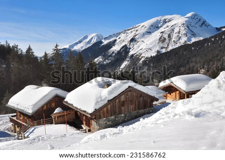 chalets in the mountains covered with snow - stock photo