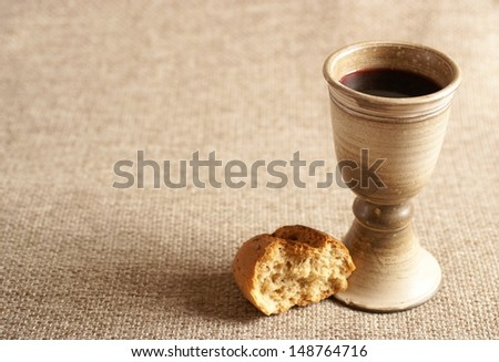 Chalice with wine and bread. Background with copy space - stock photo