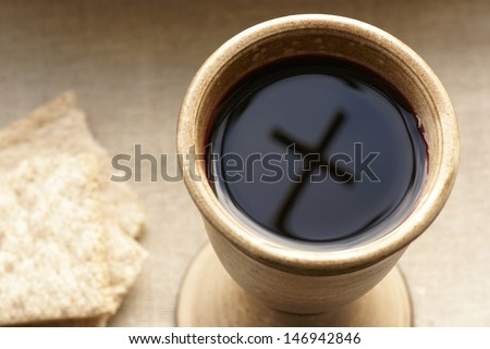 Chalice with wine and bread. Cross shadow in the chalice. - stock photo