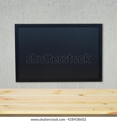 Chalk board on the wall of the school. In the foreground, an empty wooden desk - stock photo