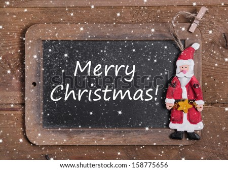 Chalk board with Merry Christmas message , santa and snowflakes on wooden background for a greeting card - stock photo