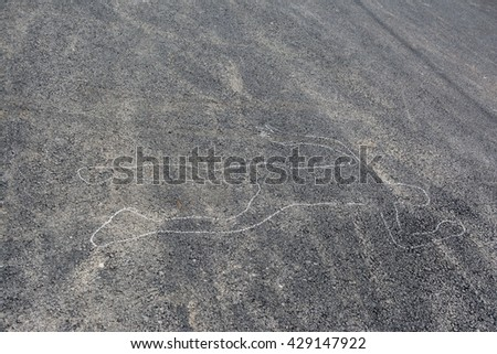 Chalk outline of body drawn on the road - stock photo