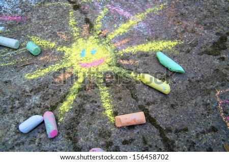 Chalk painting of a happy sun on the pavement - stock photo