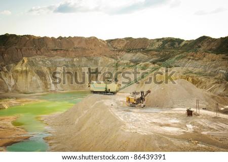 Chalk quarry landscape with big excavator - stock photo