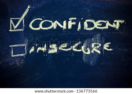 chalk writings on blackboard, choice between being confident or insecure - stock photo