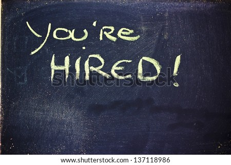 chalk writings on blackboard, you're hired - stock photo