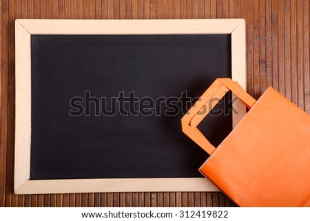 Chalkboard and shopping bag over wooden background. Copyspace. - stock photo