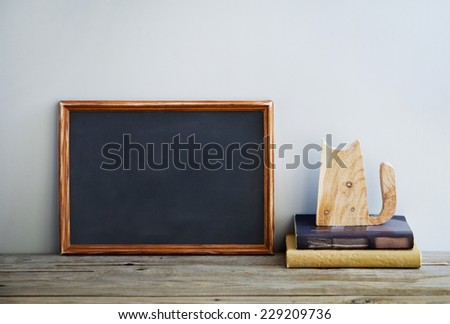 chalkboard frame on the grey wall with books and wooden cat. Place for text. Scandinavian or American style interior.