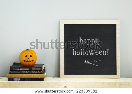 chalkboard frame on the grey wall with books  pumpkins HAPPY HALLOWEEN - stock photo