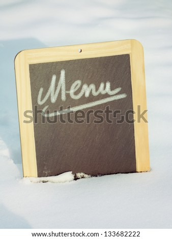 Chalkboard sign in snow with menu word - stock photo