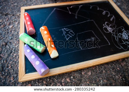 Chalkboard with a picture of a house and colorful street chalk - stock photo