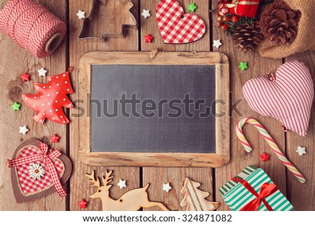 Chalkboard with Christmas decorations on wooden background. View from above - stock photo