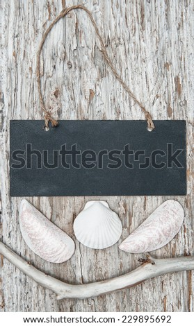 Chalkboard with dry branch and seashells on old wood  - stock photo