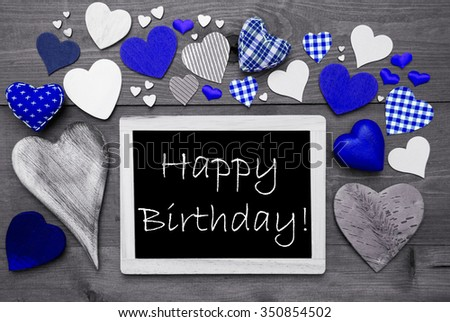 Chalkboard With English Text Happy Birthday. Many Blue Textile Hearts. Wooden Background With Vintage, Rustic Or Retro Style. Black And White Image With Colored Hot Spots. - stock photo