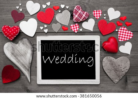 Chalkboard With English Text Wedding. Many Red Textile Hearts. Wooden Background With Vintage, Rustic Or Retro Style. Black And White Image With Colored Hot Spots. - stock photo