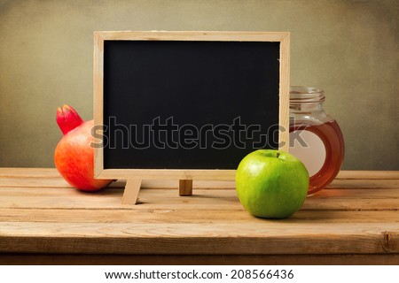 Chalkboard with honey and apple for Jewish New Year Holiday - stock photo