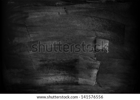 chalkboard with smeared spots from a text written in chalk - stock photo