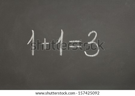 chalkboard with the words of one plus one equals three
