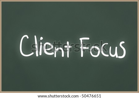 Chalkboard with wooden frame and the text Client Focus - stock photo