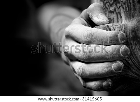 Chalked hand grips tightly to hang off an artificial climbing hold. Converted to black and white; shallow depth of field