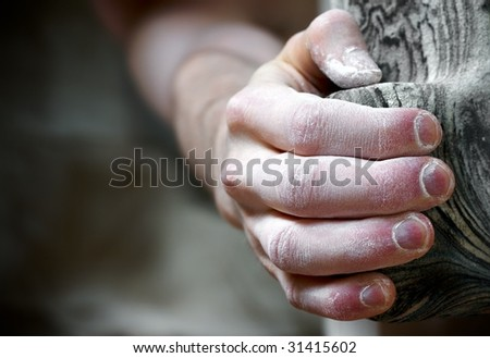 Chalked hand grips tightly to hang off an artificial climbing hold. Shallow depth of field