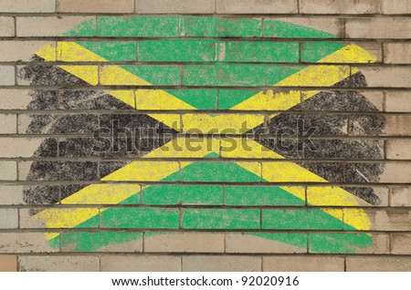 Chalky jamaican flag painted with color chalk on grunge old brick wall - stock photo