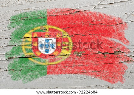Chalky portugese flag painted with color chalk on grunge wooden texture - stock photo