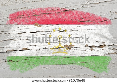 Chalky tajikistan flag painted with color chalk on grunge wooden texture - stock photo