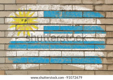Chalky uruguay flag painted with color chalk on grunge old brick wall - stock photo