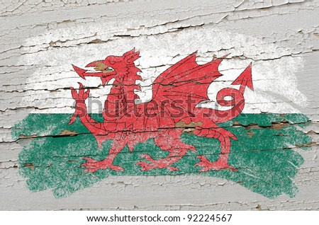 Chalky welsh flag painted with color chalk on grunge wooden texture - stock photo