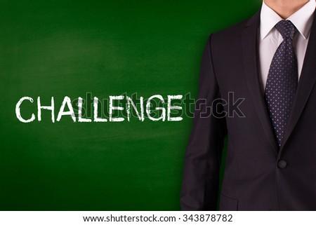 CHALLENGE on Blackboard with businessman - stock photo