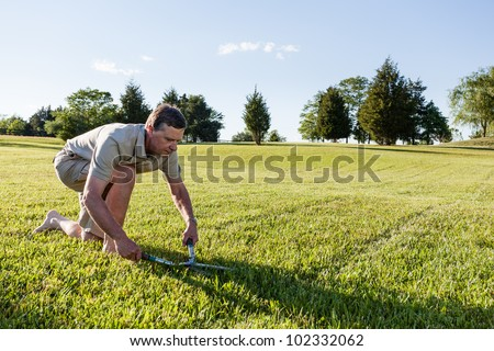 Challenging task of cutting large lawn with grass shears by hand - stock photo
