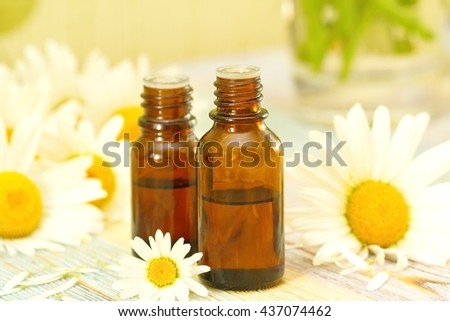 Chamomile essential aroma oil and fresh flowers - stock photo