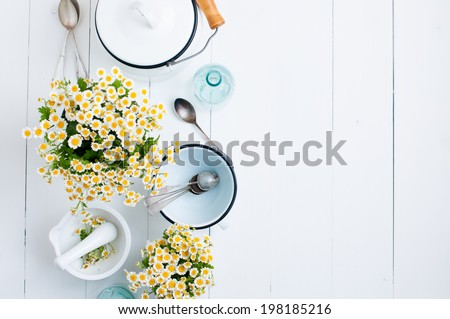 Chamomile flowers, white enamel cookware, glass bottles, vintage spoons on a white wooden background, cozy home rustic decor, vintage country living - stock photo