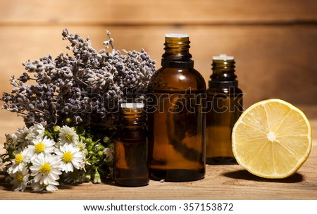 Chamomile, lemon and lavender essential oil on wooden background - stock photo