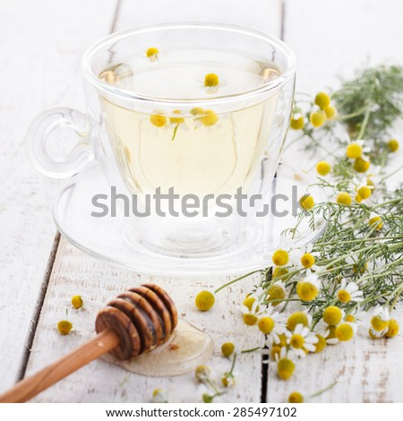 Chamomile tea and honey in a glass Cup,therapeutic.selective focus - stock photo