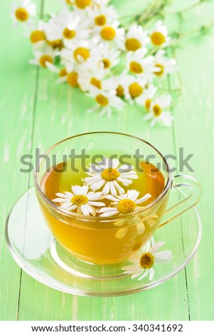 Chamomile tea in glass cup on green table - stock photo