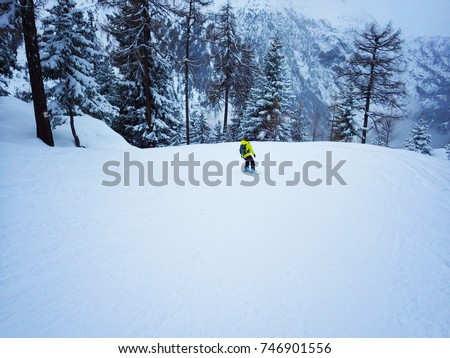 CHAMONIX, FRANCE - January 2015: Snowboarding in French Alps. Young woman on snowboard in Chamonix, France