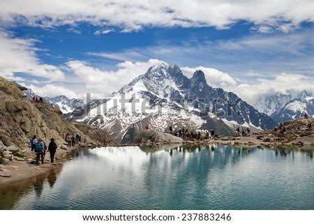 CHAMONIX, FRANCE - JULY 01, 2014: Tourists walk in Alps at Lac Blanc lake. - stock photo